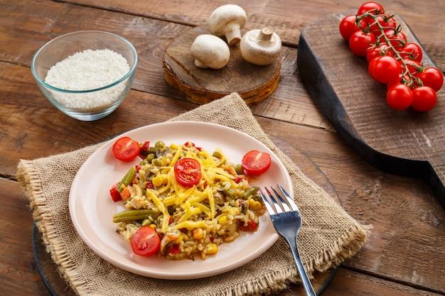 Risoto com cogumelos e queijo em um prato sobre um fundo de madeira em um guardanapo perto dos ingredientes. foto horizontal