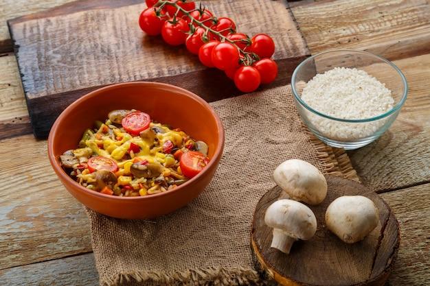 Risoto com cogumelos em um prato de barro em um fundo de madeira em um guardanapo de linho e ingredientes.