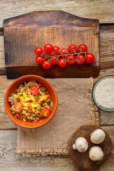 Risoto com cogumelos em um prato sobre um fundo de madeira em um guardanapo de linho ao lado de tomates em uma prancha.