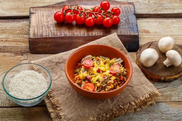 Risoto com cogumelos em um prato sobre um fundo de madeira em um guardanapo de linho ao lado de tomates.