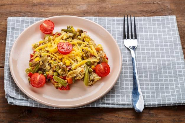 Risoto com cogumelos em um prato sobre um fundo de madeira em um guardanapo xadrez e um garfo. foto horizontal