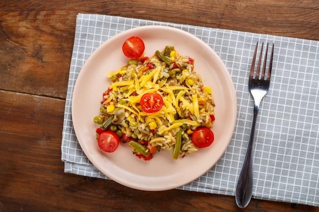 Risoto com cogumelos em um prato sobre um fundo de madeira em um guardanapo xadrez e um garfo.