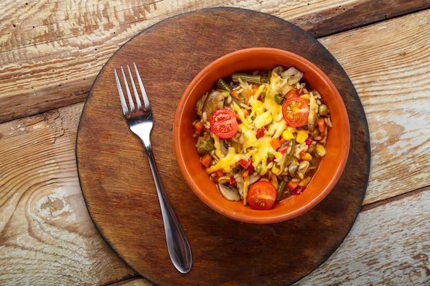 Risoto com cogumelos em um prato sobre um fundo de madeira em um suporte redondo de madeira ao lado de um garfo.