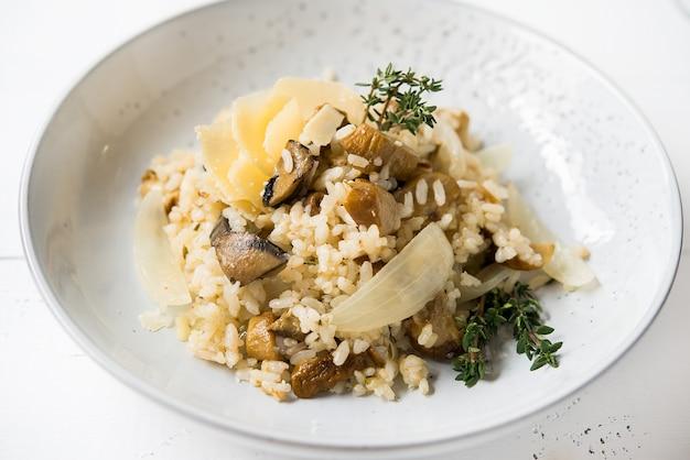Risoto com cogumelos porcini e parmesão em fundo claro, foco seletivo, close-up