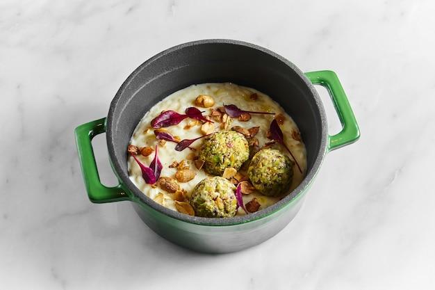 Risoto cremoso com bolinhos de aipo, amendoim e folhas de manjericão em uma panela verde sobre fundo de mármore branco