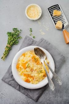 Risoto de abóbora com tomilho, alho, queijo parmesão e vinho branco em concreto cinza ou superfície de pedra. foco seletivo. estilo rústico.