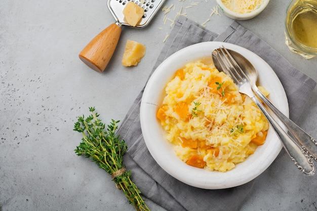 Risoto de abóbora com tomilho, alho, queijo parmesão e vinho branco em superfície de concreto cinza