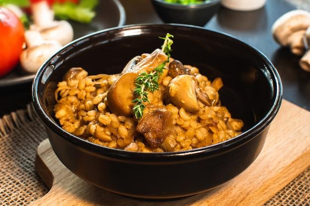 Risoto de cevada ou orzoto com cogumelos em tigela escura sobre fundo de madeira. foco seletivo.