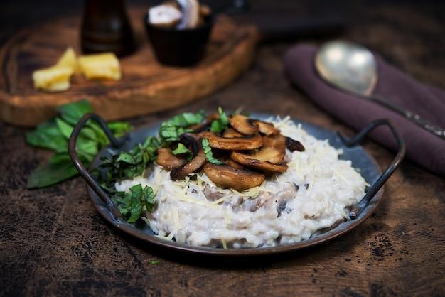 Risoto de prato italiano com cogumelos, parmesão e ervas. risoto em uma placa de cobre em um fundo marrom de madeira