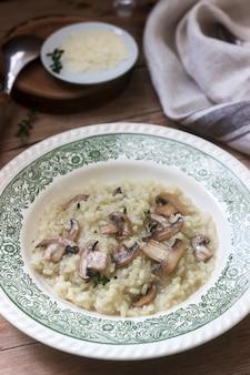 Risoto de prato italiano tradicional com cogumelos em um prato leve sobre uma mesa de madeira. estilo rústico.