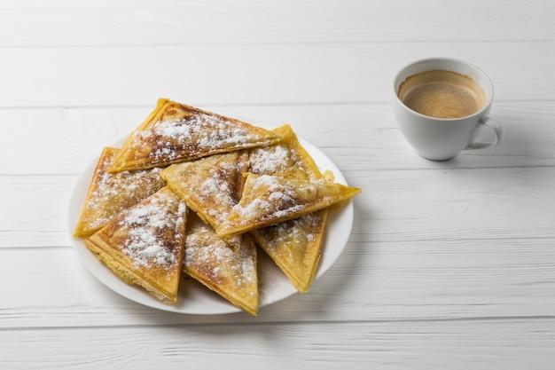 Rissóis caseiros em um prato e uma xícara de café