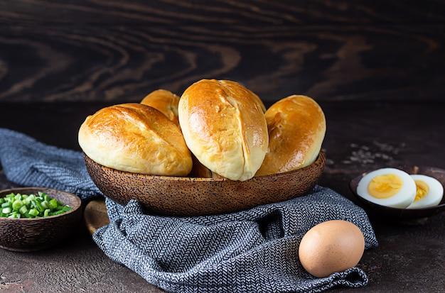 Rissóis cozidos frescos com ovo e recheio de cebola verde. pirozhki russo tradicional.