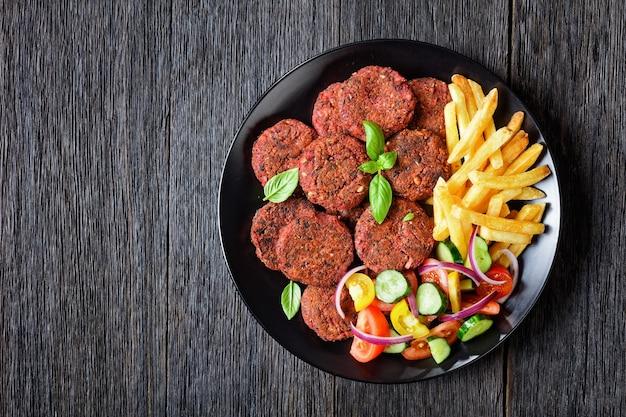 Rissóis de beterraba com cogumelos e feijão preto servidos com batatas fritas e uma salada de vegetais de tomate, pepino, cebola roxa e manjericão fresco em um prato preto sobre uma mesa de madeira escura, vista de cima, espaço livre