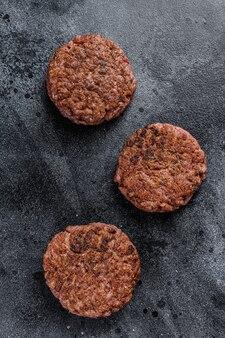 Rissóis de bife grelhado para hambúrgueres, carne picada. fundo preto. vista do topo.