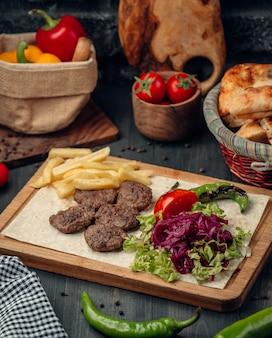 Rissóis de carne servidos com batata frita e salada verde