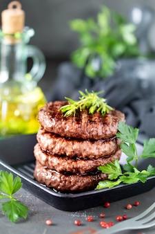 Rissóis de hambúrguer grelhado com ervas, especiarias em um escuro