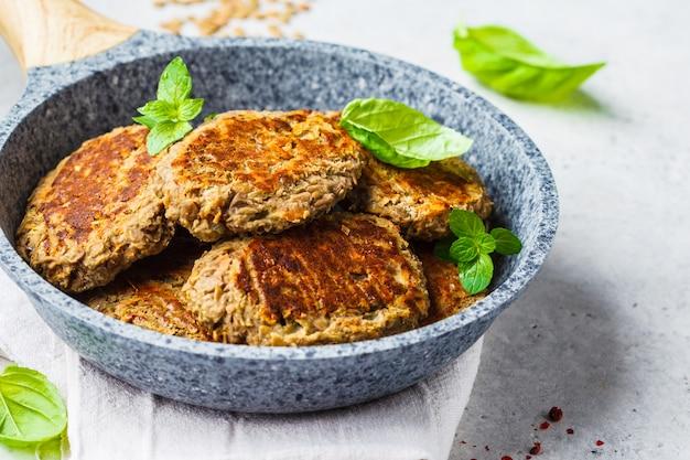 Rissóis de lentilha na frigideira cinza. conceito de comida saudável vegan.