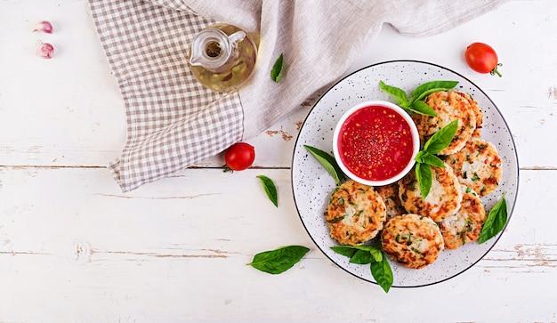 Rissóis deliciosos de arroz e carne de frango com molho de tomate e alho