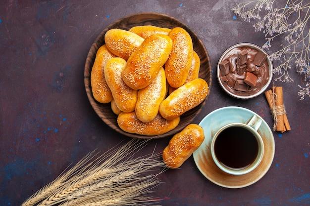 Rissóis doces de vista de cima com uma xícara de chá e chocolate no fundo escuro refeição massa massa folhada comida chá empada