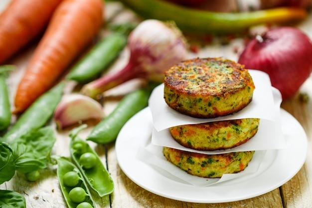 Rissóis vegetarianos saudáveis feitos de batatas, cenouras, cebolas, ervilhas, ervas e especiarias
