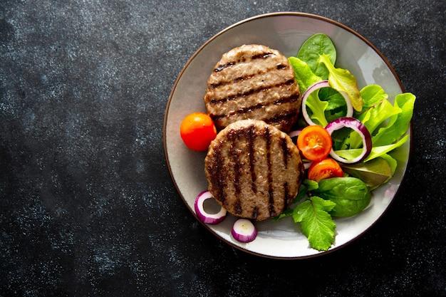 Rissol de carne picada cozida com legumes. fundo escuro.