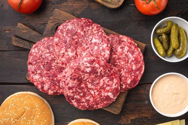 Rissol de carne picada para hambúrguer, na velha mesa de madeira escura