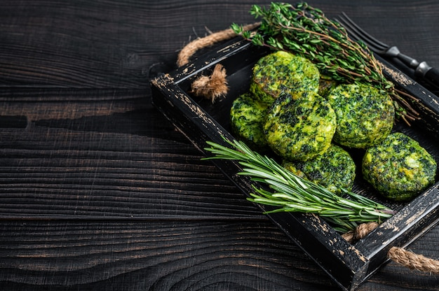 Rissol de falafel vegetal vegetariano com ervas em uma bandeja de madeira. fundo preto. vista do topo. copie o espaço.