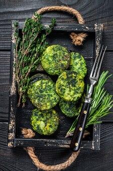 Rissol de falafel vegetal vegetariano com ervas em uma bandeja de madeira. fundo preto. vista do topo.