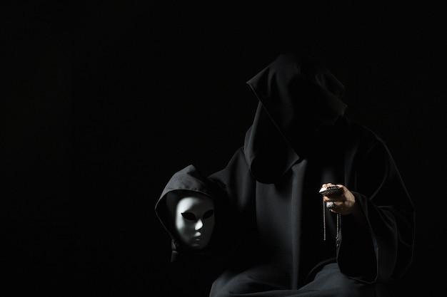 Rito de lidar com o diabo. pecador em roupas pretas e demônio na manga. homem possuído pelo diabo. feiticeiro malvado falando com máscara. schizo fala consigo mesmo. assassino amaldiçoado no quarto escuro. mago cruel.
