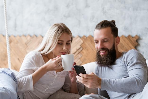 Ritual da manhã do jovem casal. discutindo planos. mulher com um copo da bebida favorita do conforto e homem com smartphone.