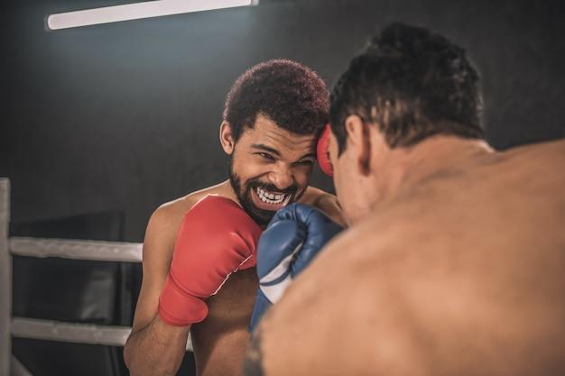 Rivalidade. dois kickboxers lutando em um ringue de boxe e parecendo agressivos