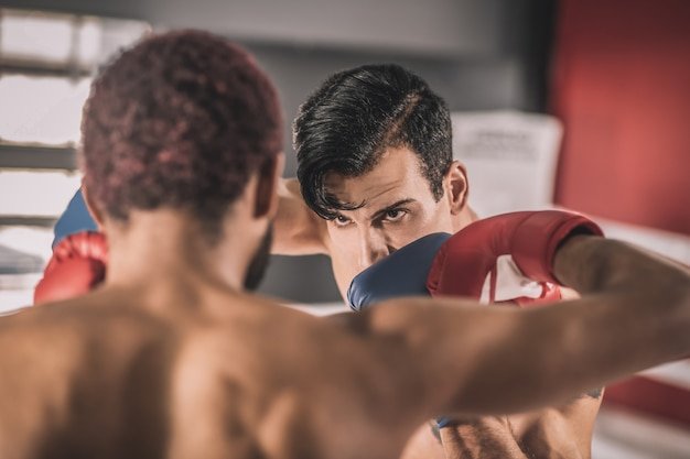 Rivalidade. dois rivais brigando em um ringue de boxe e parecendo agressivos