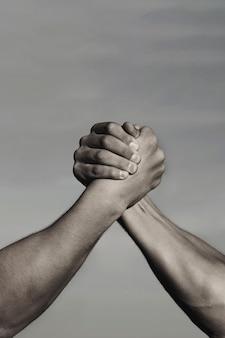 Rivalidade, vs, desafio, comparação de força. wrestling de braço de dois homens. luta livre, competição. conceito de rivalidade - close-up da queda de braço masculina. conceito de liderança. preto e branco.