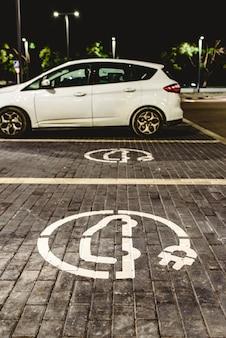 Roadsign da estação de carregamento livre do carro elétrico em um lote de estacionamento europeu do supermercado.