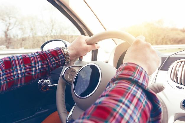 Roadtrip - mãos do homem no volante e autobahn em segundo plano