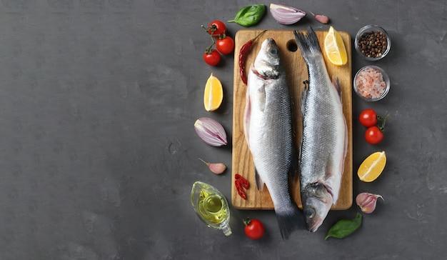 Robalo de peixe cru com ingredientes e temperos como manjericão, limão, sal, pimenta, tomate cereja e alho na placa de madeira na mesa escura. vista do topo. espaço para texto