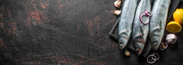 Robalo de peixe cru com limão, rodelas de cebola e alho.