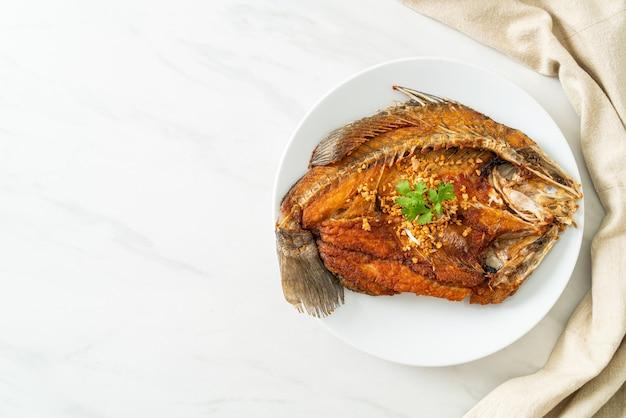 Robalo frito com alho no prato