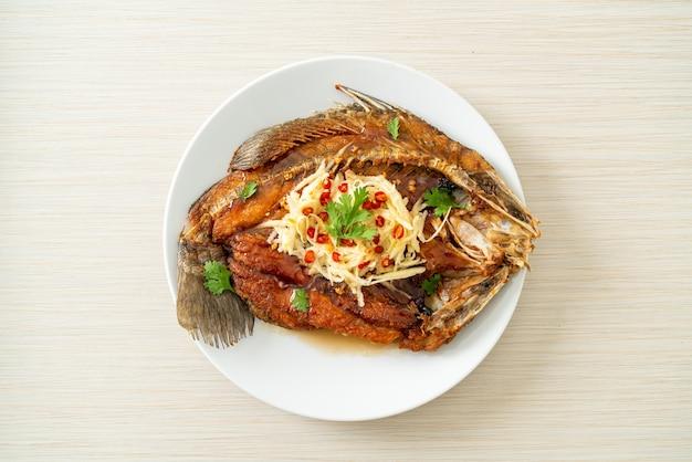 Robalo frito com molho de peixe e salada picante no prato