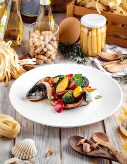 Robalo gourmet recheado de vegetais em um prato branco