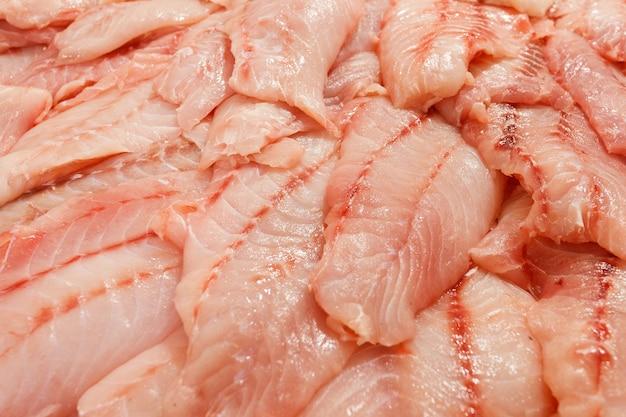 Robalo, presunto, garoupa, filé de robalo em muitos pedaços fatiados e empilhados a granel no mercado de peixes.
