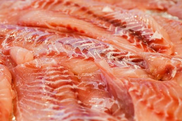 Robalo, presunto, garoupa, filé de robalo, muitos fatiados e empilhados a granel no mercado de peixes.