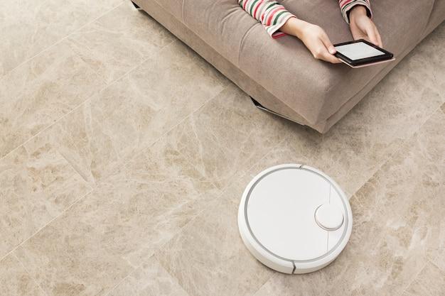 Robô aspirador de pó, limpando o quarto enquanto mulher relaxando no sofá
