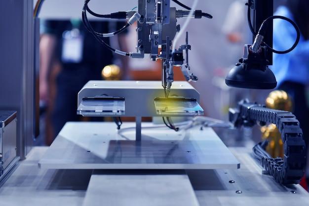 Robô automático moderno e de alta tecnologia para a máquina de montagem de placas de circuito impresso (pcb) durante a soldagem ou a soldagem de peças ou componentes na fábrica