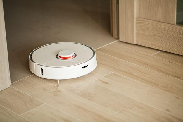 Robô de aspirador é executado no piso de madeira em uma sala de estar.