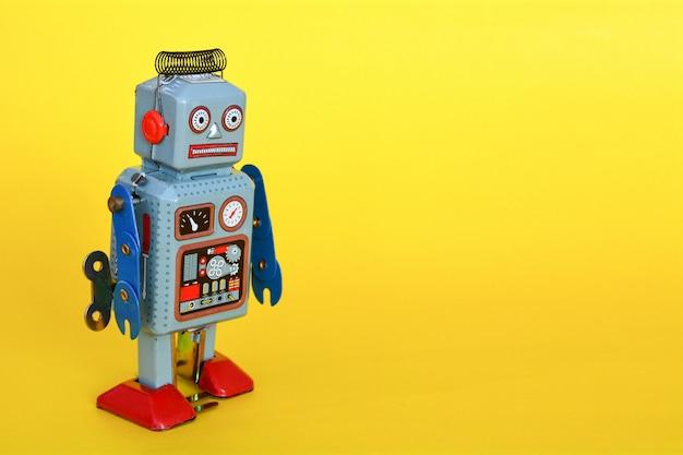 Robô de brinquedo de lata vintage isolado em um fundo amarelo.