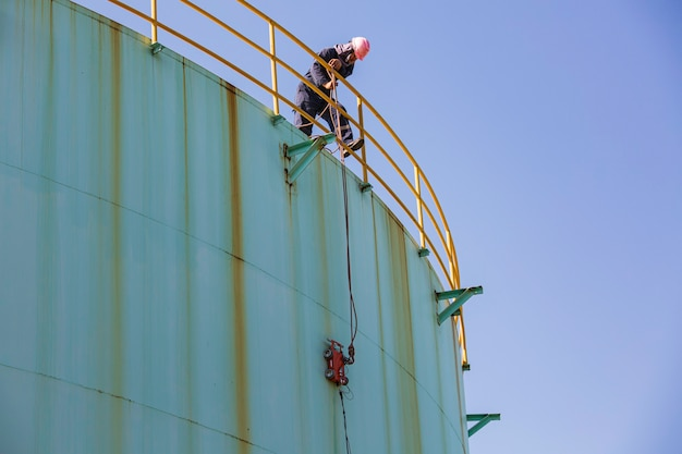 Robô de escalada de espessura de concha placa de armazenamento de óleo abaixo de trabalhador masculino puxar a corda