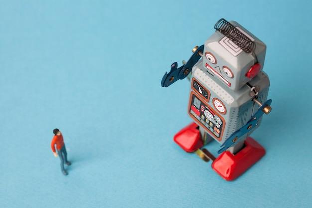 Robô de lata de brinquedo com homem sobre fundo azul