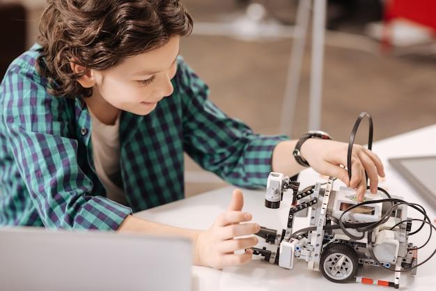 Robô do futuro. menino positivo e encantado capaz de sentar na escola e usar um gadget digital enquanto estuda e expressa alegria
