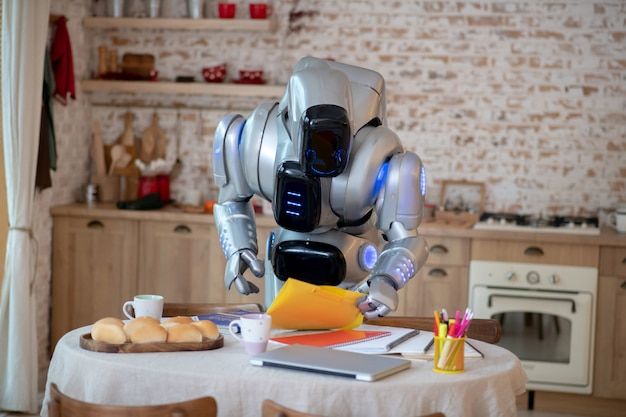 Robô em pé enquanto olha para livros e cadernos da mesa